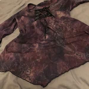 Långärmad lila blus med utsvängda ärmar och knytning fram till