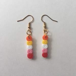 Egengjorda nickelfria örhängen inspirerade av lesbiska flaggan 🧡💛🤍💖❤️ Fler prideflaggor finns på min sida!