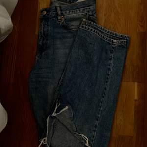 Raka jeans från junkyard med ett hål på ena knät