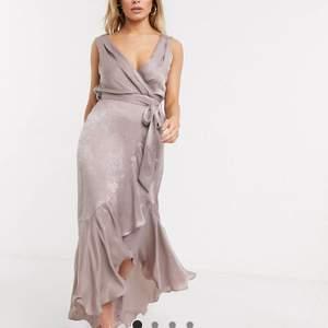 Ljus lila/rosa klänning från asos i satin liknande tyg med omlott framtill. Jättefin till fest, bal, bröllop! Använd 1 gång