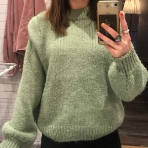 Detta är en grön stickad tröja som är köpt på Gina tricot. Den är oversized i modellen och har superfina volanger vid armen