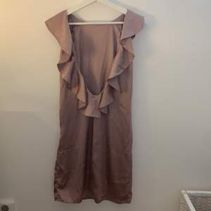 Söt rosa/lila/champagne färgad klänning. Öppen rygg och volanger som detalj. Finns en dragkedja på ena sidan. Mycket bra kvalite, använd en gång💜💕 Hör av er vid frågor, frakt står köparen för🚚