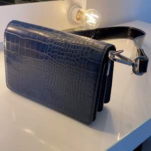 Axelremsväska från märket DON DONNA. Marinblå snakeprint med svart avtagbart lackband till. Använd max 3 gånger och är i väldigt gott skick. Köpare står för frakt.