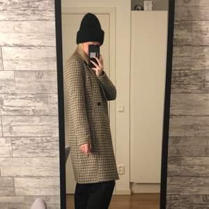 En kappa från Vero Moda i ett rutigt mönster med svart, vitt pch beige/bruna färger. Har två fickor och går att stänga med två knappar i mitten. Kappan går precis nedanför mina knän på mig och jag är 165 cm. Kappan är relativt tjock, jag hade den år 2019 och använde den under hösten/vintern.