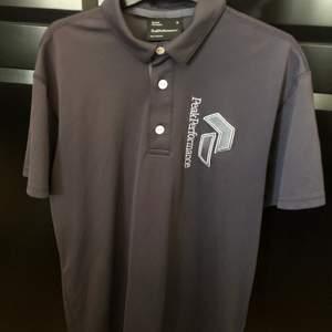 Blå/lila golf piké ifrån PeakPerformance i 100% polyester. Storlek M I väldigt fint skick. Mitt pris 300kr inkl Nypris ca 600kr