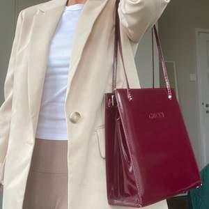 """En vintage väska med GUCCI """"ingraverat"""" på framsidan. Hård i strukturen och rymlig inuti. Helt fungerade dragkedjor. 🖤 DM vid frågor. Budgivning avslutas måndag 26/4, kl 18:00."""