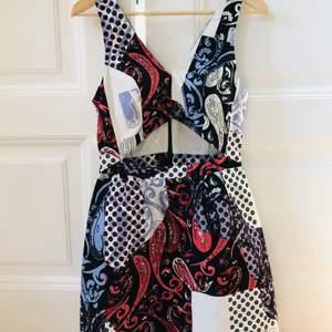 Kort mönstrad klänning med cut-out ovanför midjan från Topshop. Storlek 38 men skulle snarare säga att den passar en 36a. Dragkedja i ryggen. Sparsamt använd. Säljer pga att den blivit för liten.