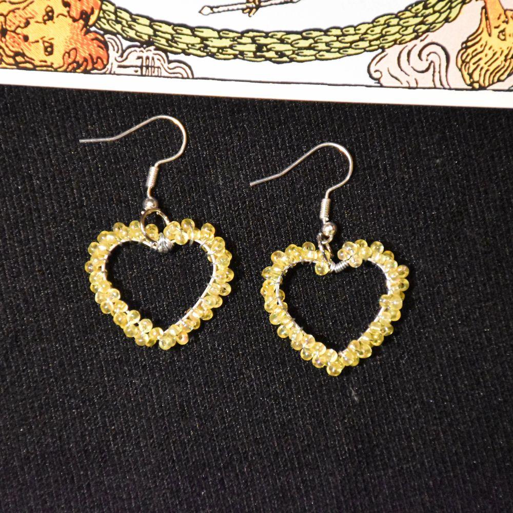 Örhängen i formen av hjärtan med gula glänsande pärlor! Krokarna är nickelfria.  . Accessoarer.