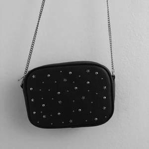 Svart väska med nitar och stjärnor. Köparen står för val och kostnad av frakt