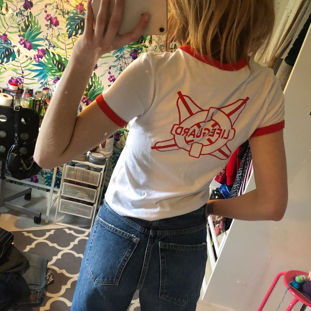 """Vit tshirt med röda detaljer och """"Lifeguard"""" som tryck på ryggen och """"HAWKINS POOL"""" på framsidan. Använd ca 2 gånger. Köparen står för frakt💕. T-shirts."""