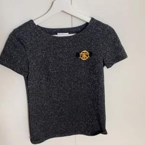 En superfin och varsamt använd T-shirt från Ida Sjöstedt. T-shirten är svart och glittrig. Ett guldigt Ida Sjöstedt märke på vänstra bröstet. Använd endast ett fåtal gånger.