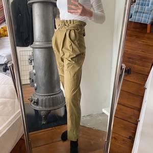 Superfina gröna högmidjade paperbag byxor från Mango i storlek 34/XS. Jag är 174 cm lång och de är som man kan se lite kortare i benen på mig. Superfint skick då jag endast använt dessa tre gånger.