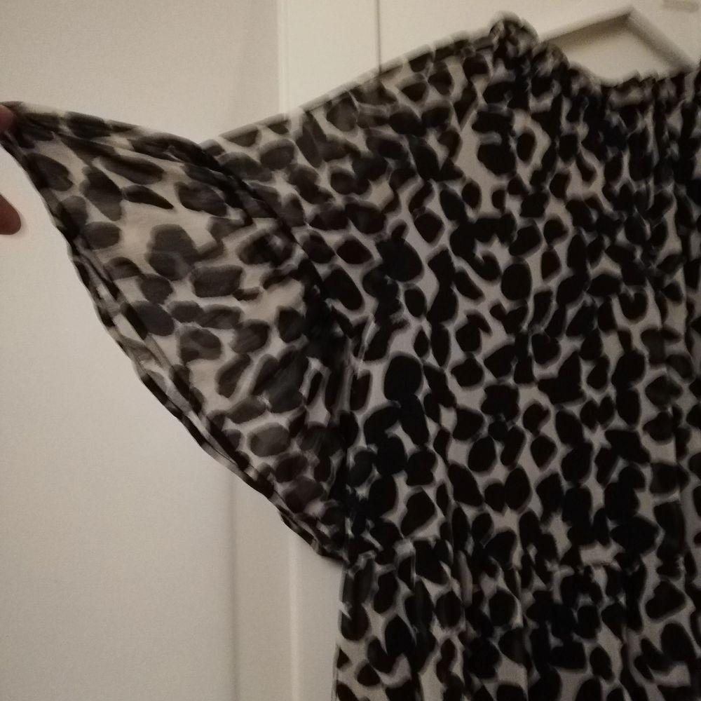 Luftig och lös klänning med svarta fläckar på benvit bakgrund. Har knytning i nacken. Jag har haft den på mig 2 ggr med svart skärp. . Klänningar.