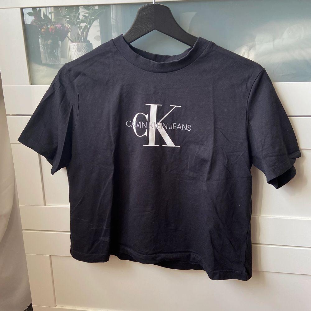 Svart t-shirt från Calvin Klein i ganska croppad modell. Använd men i fint skick, storlek S men skulle säga att den även passar en XS. 150 kr inklusive frakt. . T-shirts.