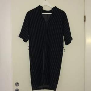 """En varm klänning med """"bälthållare"""", aldrig använd och från okänt märke."""