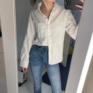 Vit enkel skjorta som både är fin under en stickade tröja eller med ett par snygga jeans! Lite oversized i modellen.