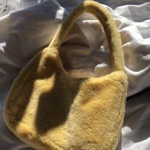 Gul fluffig väska från monki. Knappt använd och i jätte bra skick samt kvalitet. Säljer då den aldrig riktigt kommit till användning. Original pris: 180 kr. Buda endast om ni kommer stå för erat bud 💕