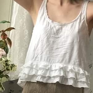 Sött vitt linne med volanger och spetsdetaljer från hollister. Sparsamt använt.