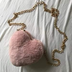Liten supersöt fluffig hjärtformad axelremsväska med gulddetaljer. Aldrig använd.