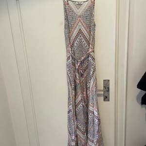 Somrig långklänning i fint mönster med smala band samt ett smalt band till midjan. Knappt använd i fint skick