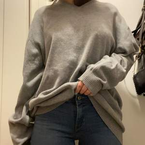 Snygg grå stickad tröja med v-uringning. Storlek L och sitter mycket oversized på mig som brukar ha XS-S. Funkar som tröja eller klänning. Bra kvalitet och i nyskick