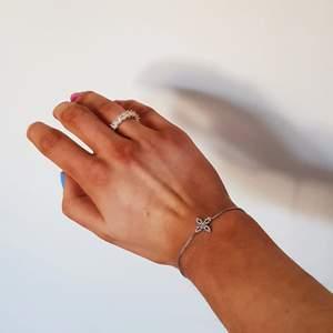 Justerbart armband i silver med fin detalj i form av figur liknande en blomma prydd med små kristaller. Ej använt så som nytt.
