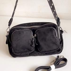Svart väska med silver detaljer från Gina tricot, aldrig använd (därför de ligger papper i) tillkommer ett extra band som är längre. Extremt mycket utrymme. 2 större fack, 1 mindre inuti och två små fack på utsidan.
