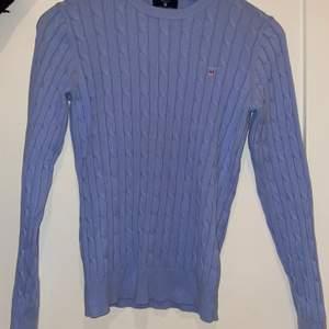 En ljus blå Gant kabelstickad tröja i bra skick. Storlek S.