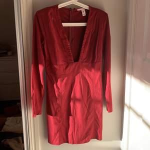 """Röd klänning från nly trend. Storlek M. Det är små inlägg i axlarna så att det blir """"puffaxlar"""". Dragkedja i ryggen"""