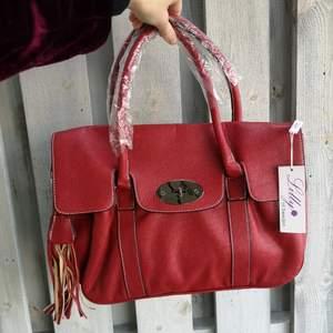 Helt ny oanvänd röd väska i syntetskinn från Lilly of Sweden. Den är rymlig med bred botten, har tre fack på insidan varav ett med dragkedja och tillhörande nya axelband i passande färg.  Storlek; Längd 36cm Höjd 26cm Bredd 15cm