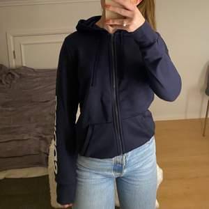 Marinblå hoodie från adidas, med tryck på ärm