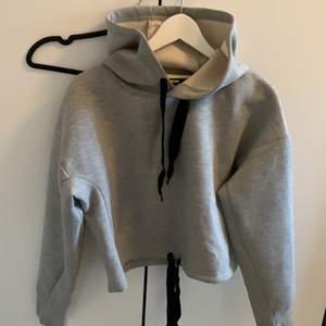 Grå hoodie från Bikbok i storlek S, går att knyta i midjan för att göra den kortare. Endast använd 1 gång.
