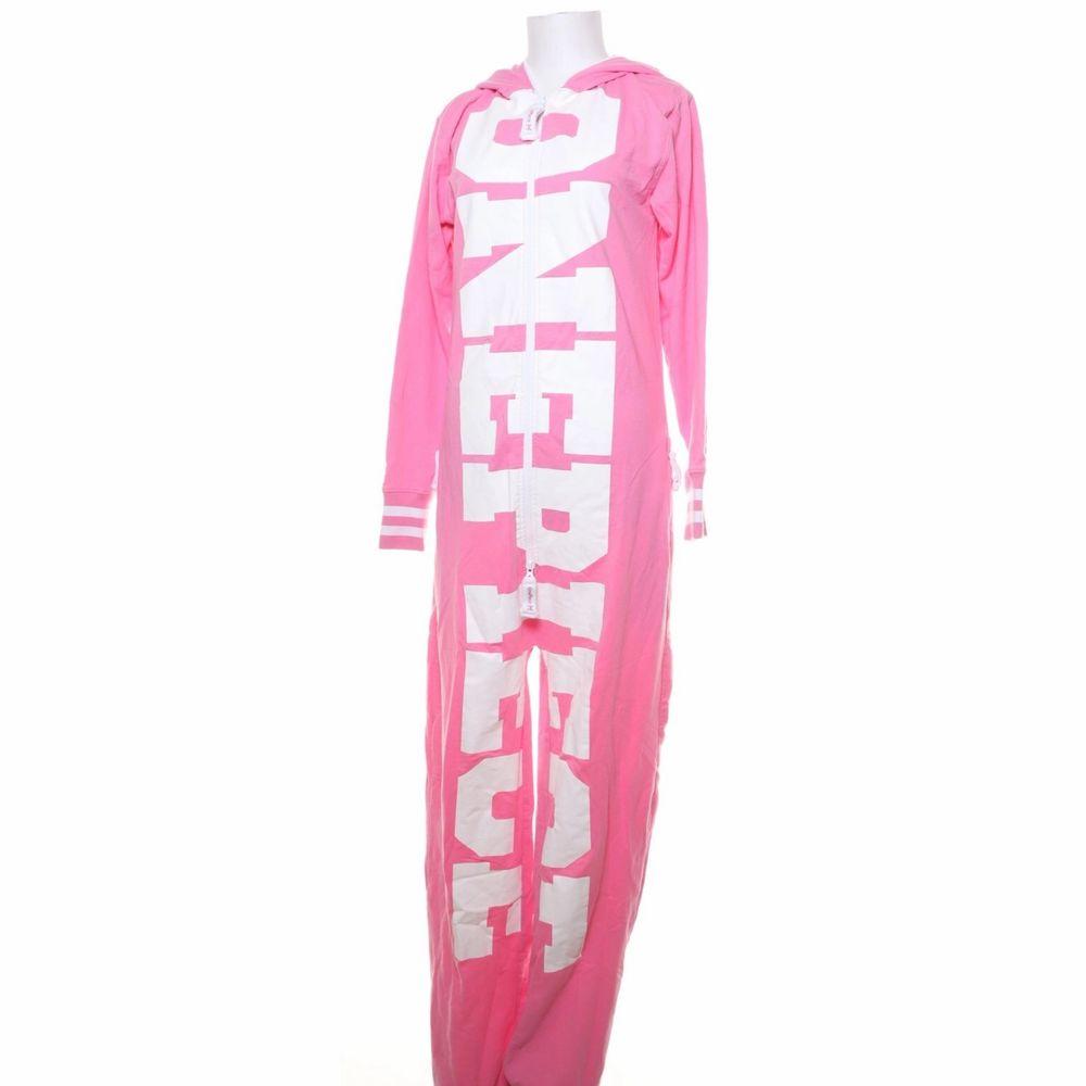 Nostalgisk onepiece i rosa med stor vit logga. Huvtröjor & Träningströjor.