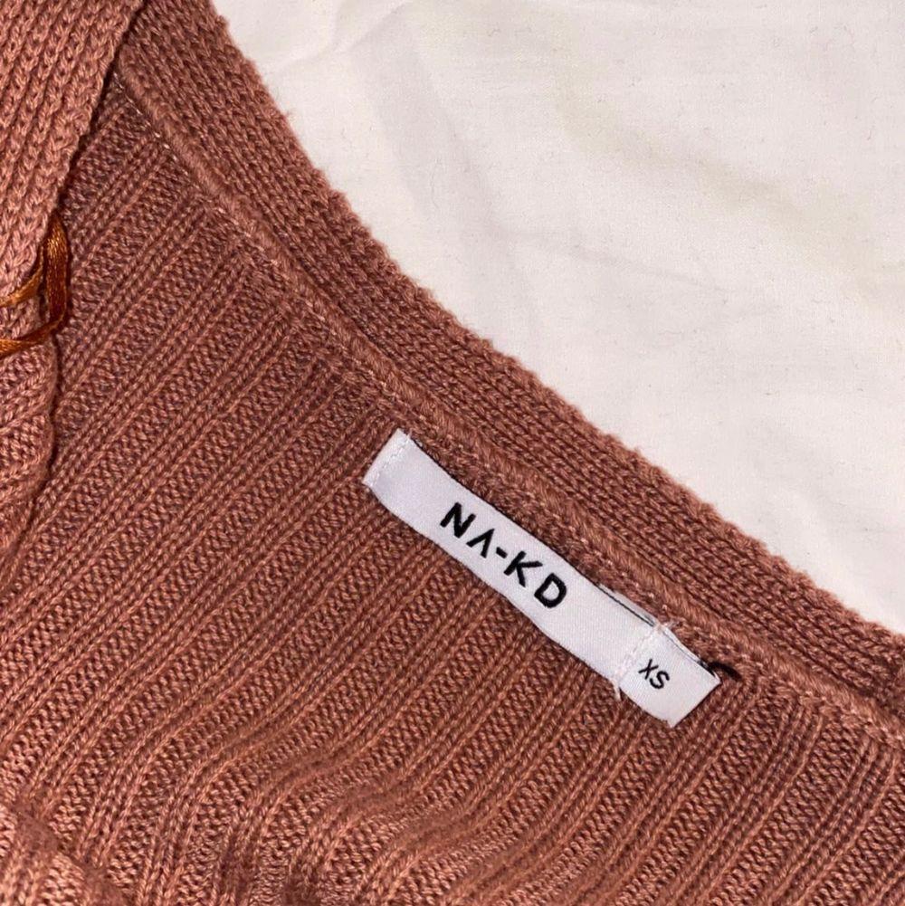Supersnygg omlott tröja med knytning från nakd! Den går att knyta på flera olika sätt! Säljer för att den aldrig kommer till användning! Nyskick💞💞. Toppar.