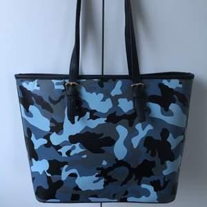 Supersnygg väska i blå camo! Säljs då den tyvärr inte kommer till användning 🥺 är i jättebra skick och har bra med fack på insidan, skriv för fler bilder ❣️ säljes först till kvarn eller högsta bud! Frakt tillkommer!!