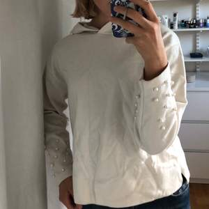 Stickad gräddvit hoodie från zara med pärlor på ärmarna och på luvan. Använd fåtal gånger så jättefint skick!