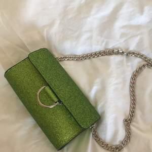 Grön glittrig axelbandsväska. Aldrig använd och är som ny.