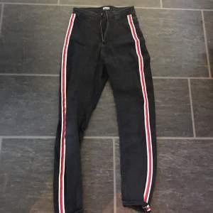 Svarta jeans ifrån Zara med röd,svart o vita ränder på sidan av byxan. Säljs pga inte använt på ett tag. Strl 36. Sitter väldigt bra!