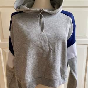 Säljer en mjuk Hoodie från H&M i storlek L. Färg: grå med inslag av vitt och blått. Dragkedja, huva och lite kortare modell.