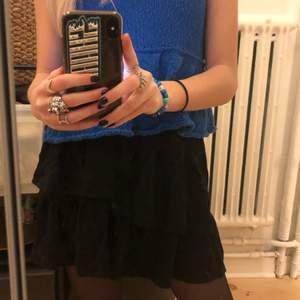 Skitsnygg svart volang kjol med knytning i midjan från H&M i strl 158/164!! Använd fåtal gånger ⭐️ Köparen står för frakt.