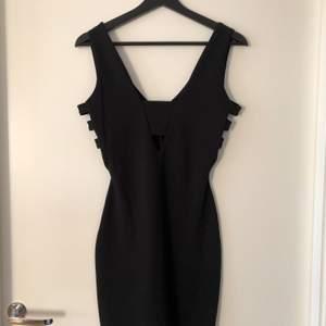 Tight svart bodycon klänning. V-ringad fram och bak. 3 straps på sidorna. Stl 34 i EUR, 8 i UK. Använd 2 gånger.