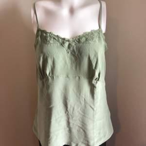 Fint ljusgrönt linne i 100% siden. Oanvänt. Nypris 600:-