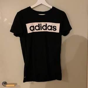 Svart Adidas t-shirts i storlek M . Med stort tryck över bröstet.