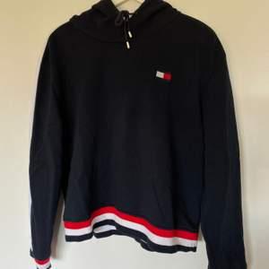 Något croppad hoodie från Tommy Hilfiger. Inköpt i TH-butik i Los Angeles för ca 700kr. Mörkblå med ränder längs armar samt på muddar. Är i storlek XL men passar M-L! Skickas spårbart för 63kr 🤩