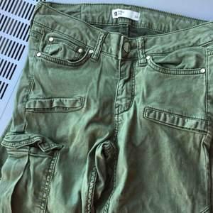 Ett par lågmidjade militär gröna jeans med ficka på ena låret. ifrån Gina tricot. Använda en gång. Köpta för 499kr med säljer för 120kr. Pris kan diskuteras!
