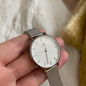 En super fin silvrig Daniel wellington klocka som är i ett bra skick, då den sällan är använd! Säljer på grund av att jag inte använder mig av den! Den är som går att göra större samt mindre beroende på  ens handled.