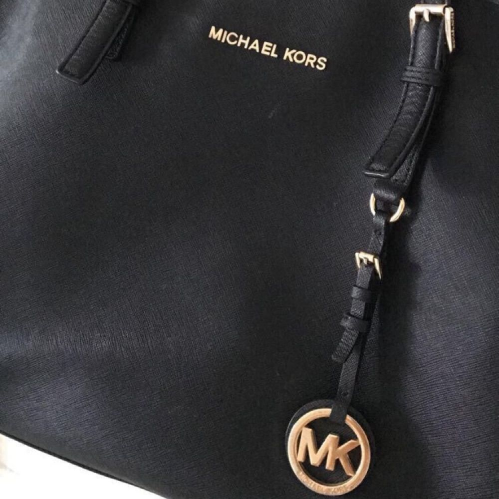 Svart Michael Kors väska med guldiga detaljer i Jet Set modellen. Mycket praktisk med många olika fack där både datorer och böcker får plats. Fint skick, men litet slitage på MK märket, som man däremot endast ser från nära håll.. Väskor.