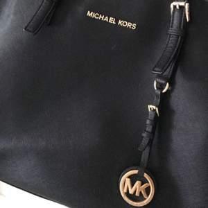 Svart Michael Kors väska med guldiga detaljer i Jet Set modellen. Mycket praktisk med många olika fack där både datorer och böcker får plats. Fint skick, men litet slitage på MK märket, som man däremot endast ser från nära håll.