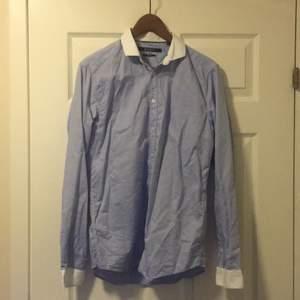 Herrskjorta från Tiger, självklart äkta. I ljusblått tyg med vita ärmslut och krage. I fint skick, nypris var 899 kr.