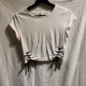 En vit T-shirt med detalj i midjan vilket ger illusionen av en lite mindre midja. Väldigt fin även om den är enkel. Används inte längre och säljs därför. Plagget är i gott skick.